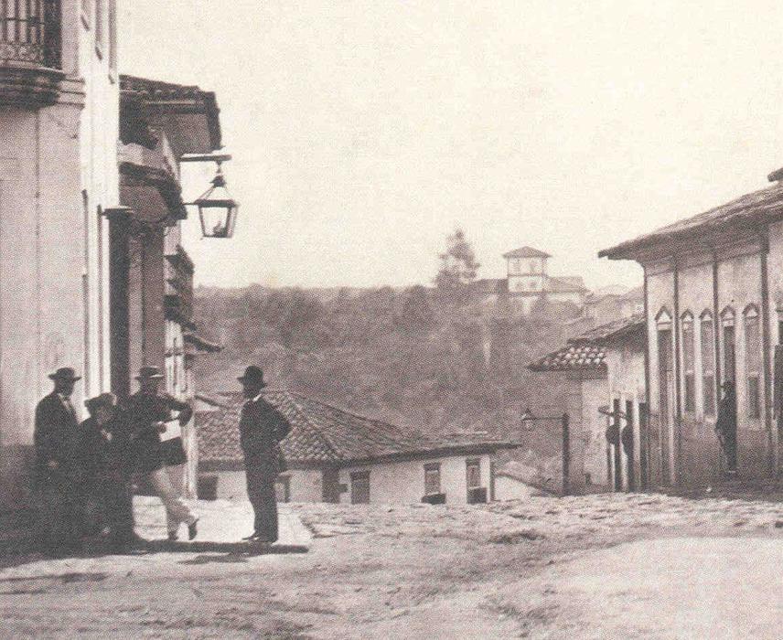 Em detalhe de imagem de Militão Augusto de Azevedo feita em 1862, vê-se a convivência das luminárias presas às residências com aquelas afixadas em postes de madeira (ao fundo)<a style='float:right' href='https://www3.al.sp.gov.br/repositorio/noticia/hist/Ilumina__Milit_o.1862.jpg' target=_blank><img src='/_img/material-file-download-white.png' width='14px' alt='Clique para baixar a imagem'></a>